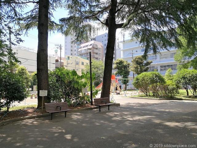 赤羽公園の小さな公園近くの木々に囲まれたベンチ