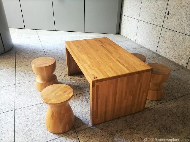 KITTE名古屋B1F屋外階段出入口にある木製4人掛けテーブル席