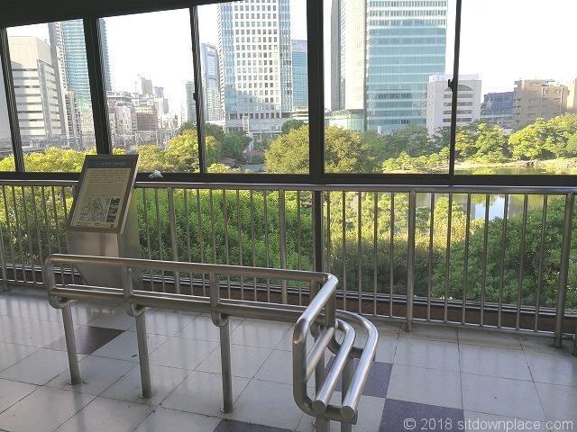 浜松町駅歩行者通路のベンチと旧芝離宮恩賜庭園の景観