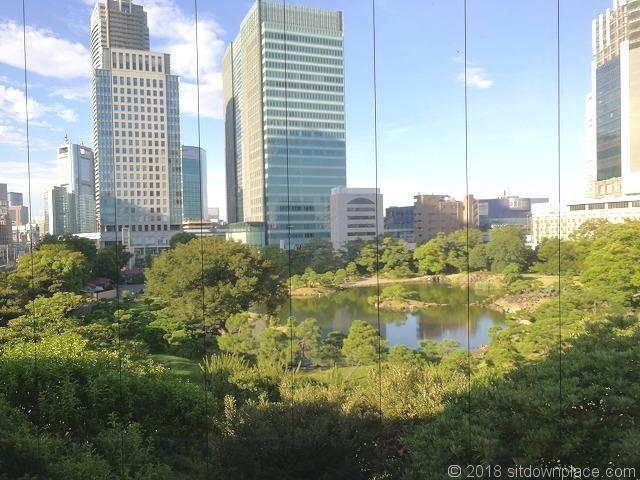 浜松町駅歩行者通路の窓ガラスからの旧芝離宮恩賜庭園の景観