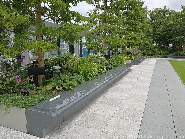 銀座シックス屋上庭園の芝生付近にある石材ベンチ