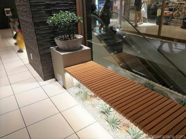 北千住マルイ9Fレストラン街のエスカレーター横の木製ベンチ