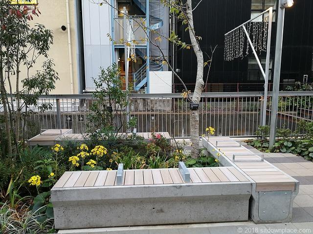 渋谷川沿いのL字型に配置された3人掛け木製ベンチ