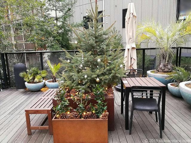 代々木ビレッジbykurkkuの2Fデッキのツリーとテーブル席